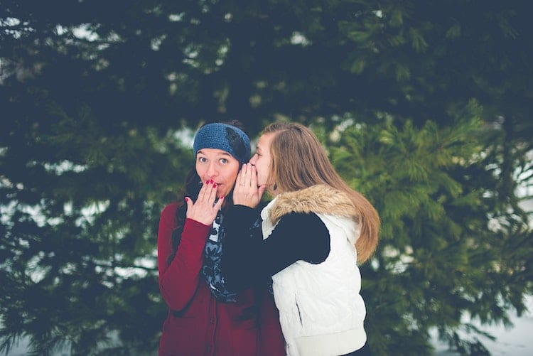 Woman whisper to her friend.