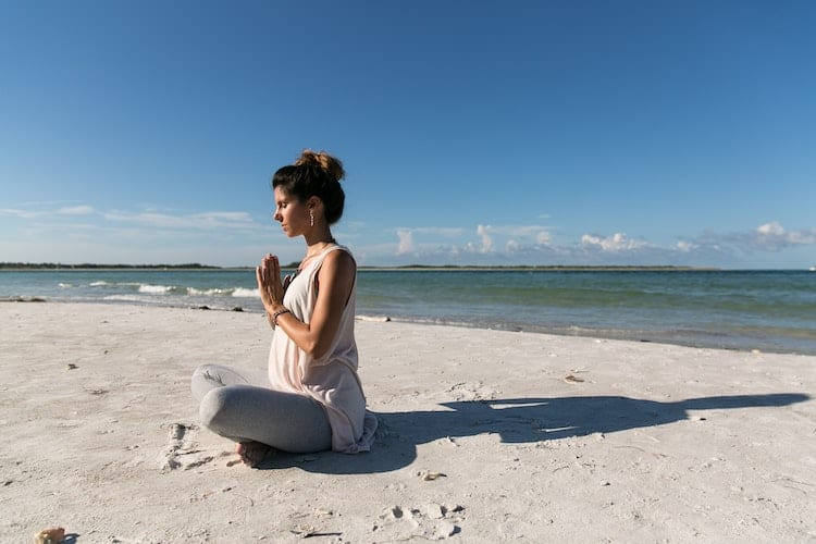 Woman is meditating on the beach.